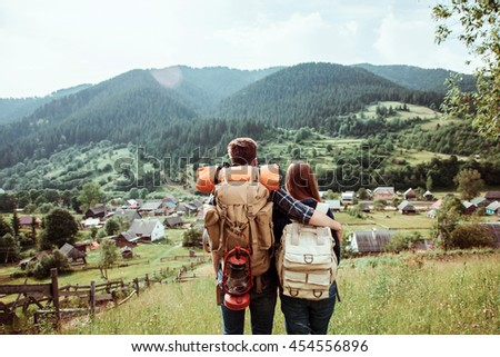 A couple of tourists in time of trip steel and admire the beautiful mountain scenery. The guy hugs the girl. The concept of love, tenderness and recreation