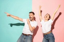 A couple of young funny and happy man and woman dancing hip-hop at studio on blue and pink trendy color background. Human emotions, youth, love and lifestyle concept