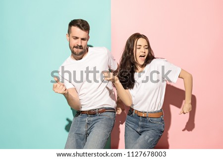 Photo of A couple of young funny and happy man and woman dancing hip-hop at studio on blue and pink trendy color background. Human emotions, youth, love and lifestyle concept