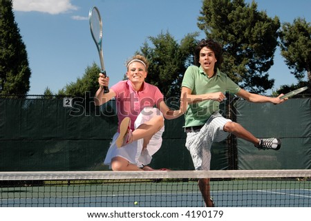 A couple of young tennis players jumping over the net