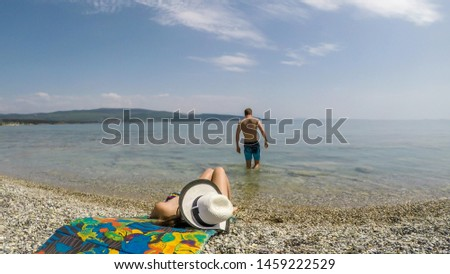 A couple on the beach. The girl is lying on a mat and suntanning, whilst the man is going into the sea. Couple travels. Stony beach and turquoise color of the water. Clear and sunny day. #1459222529