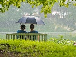 A couple on the bench under umbrella