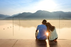 A couple on the wooden port at a lake on sunset.