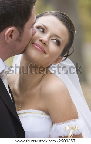 A couple on their wedding day kissing and laughing