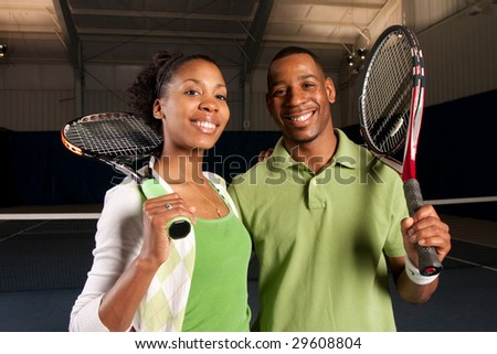 a couple posing next to a tennis court