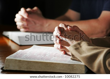 A couple prays together at a table as their hands rest upon their Holy Bibles (Shallow focus).