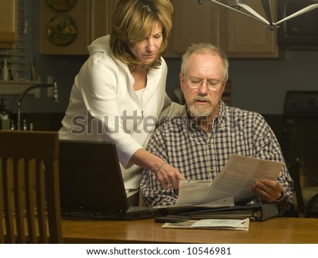 a couple read financial statements at home