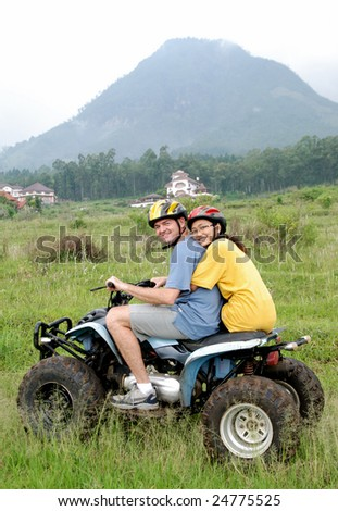A couple ride an ATV