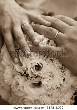 A couple's hands with wedding rings on a bouquet