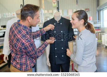 a couple selecting a uniform #1521068165