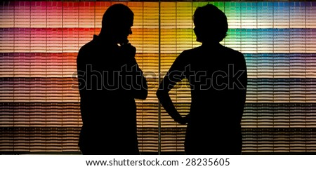 A couple selecting paint samples from a paint store color chart