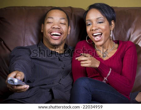 A couple shares a good laugh while watching something funny on TV - stock photo