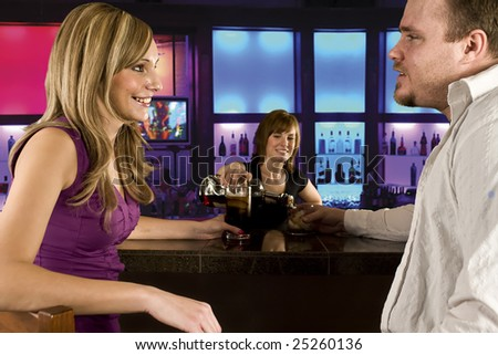 A couple sitting at bar with bar tender pouring a drink