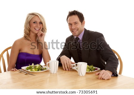 A couple sitting at dinner with nice clothes on smiling and enjoying themselves.