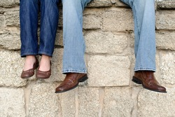 A couple sitting on an old wall dangling their feet.  Their faces are not shown.