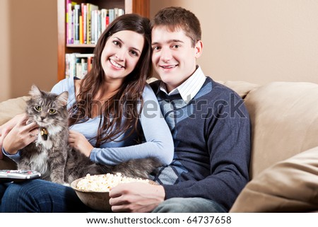 A couple sitting on sofa relaxing at home