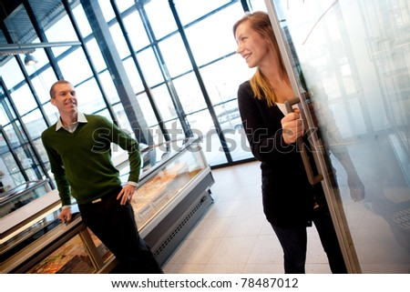 A couple smiling at each other in a supermarket, shallow depth of field, focus on woman.