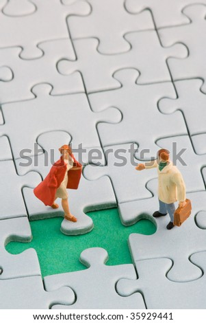 A couple standing in front of a missing jigsaw puzzle piece