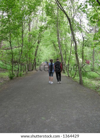 A couple strolls down a tree lined path.