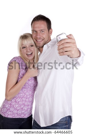 A couple taking a picture on his cell phone, she has her thumb up with happy smiles on their faces.