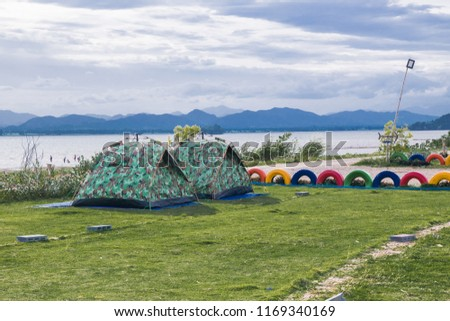 A couple tent is camping on the green grass field  near the river with blue sky and mountain #1169340169