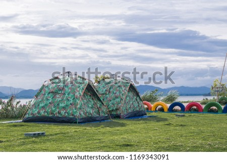 A couple tent is camping on the green grass field  near the river with blue sky and mountain #1169343091