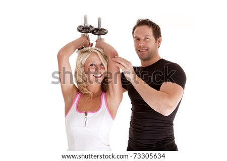 A couple together working out with weights with smiles on their faces.