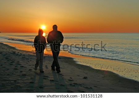 A couple walk together along the beach at sunrise