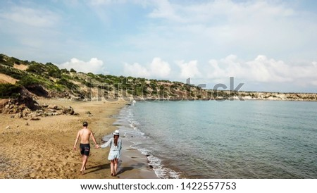 A couple walking along Lara Beach in Cyprus. Hidden gem, not spoiled by tourists. Solitude and calm feelings, waves gently spreading on the beach. turquoise color of the water. Turtle hatching beach #1422557753