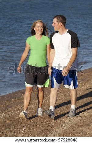 A couple walking along the beach by the water talking and smiling.