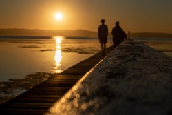 A couple walking on a jetty into the sunset