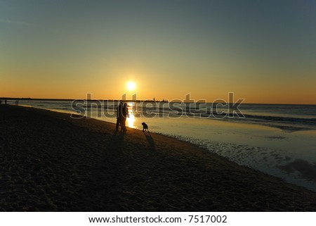 A couple walking their dog at sunset - stock photo