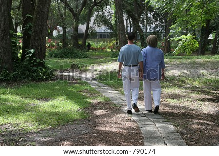 A couple walking together on garden path.