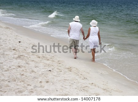 A couple walking together on the beach in Gulf Shores Alabama.
