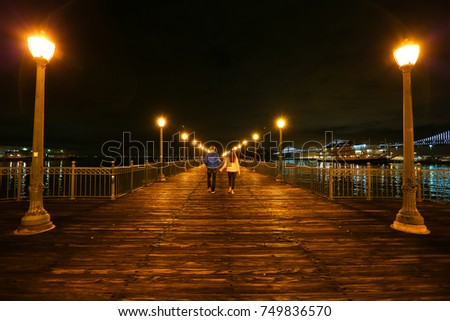 A couple walks down a pier in San Francisco California, USA. ストックフォト ©