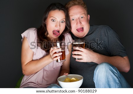 A couple watching a scary movie and it scared them so much that they are screaming.