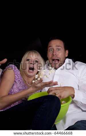 A couple watching a scary movie and it scared them so much that they threw the popcorn.