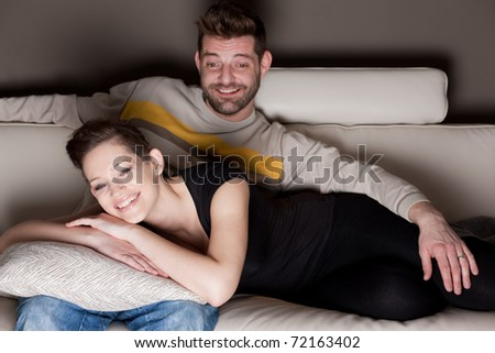 A couple watching TV on a sofa.