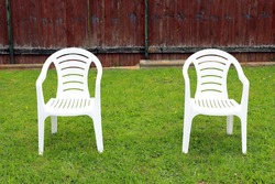 A couple white plastic chairs stands on a green lawn background in the village. Self-isolation. Social distancing. Coronavirus pandemic.