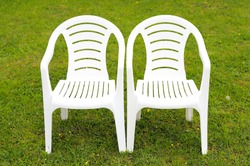 A couple white plastic chairs stands on a green lawn background in the village. Wedding decoration for guests. Interior details.