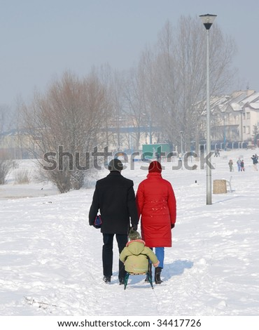 A couple with a child on sled walking in the snow
