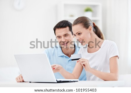 A couple with a credit card and a laptop at home