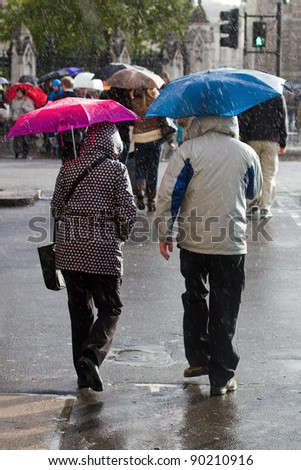 a couple with open umbrellas crossing the street
