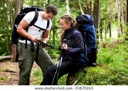 A couple with smiles looking at a map in the forest