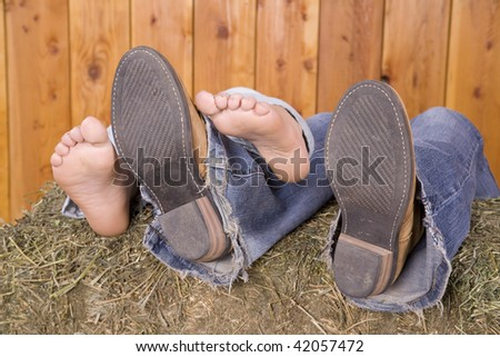 A couple with their feet stacked together on a hay bale.