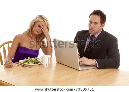 A couple with unhappy expressions on their faces, because the man is working on his computer instead of giving his woman some attention.