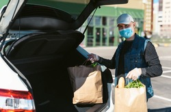 A courier in a protective mask and medical gloves delivers grocery bags from the supermarket. Auto trunk in the background. Social distancing. Coronavirus Covid 19 quarantine delivery