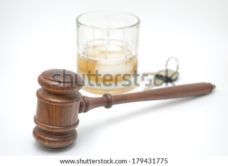 A courtroom gavel with a deliberately blurred background of highball glass and hard liquor with ice cube, and keys
