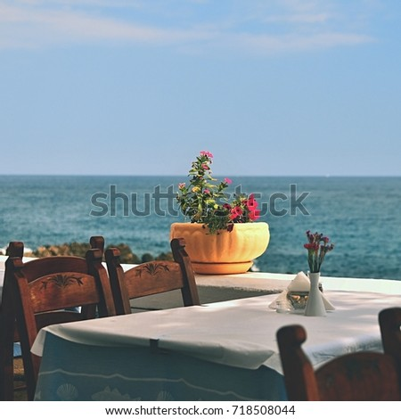 A covered table in a Greek tavern with sea. Summer background for travel, holidays and food and drink at the restaurant.