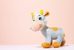 a cow toy on a pink pastel background with a copy of the space. Children's toy